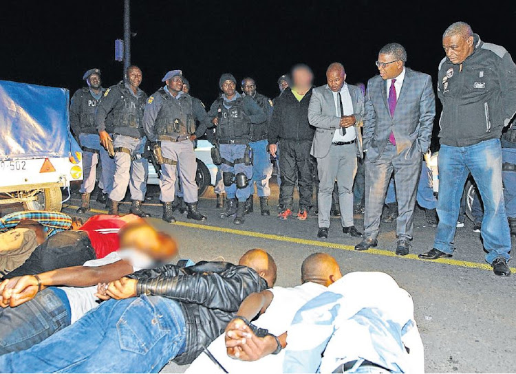 Police Minister Fikile Mbalula is photographed near eight men who the SAPS Western Cape suggested were involved in the violence in Marikana informal settlement in Cape Town. The image was released in a media statement but was soon recalled, yet still tweeted by the minister two days later.
