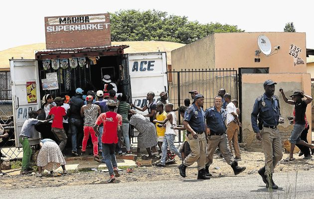 South African police walk away from the scene of a looting in progress in White City,  Soweto. Photo: Alon Skuy/The TImes