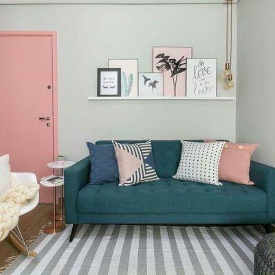 Sala com composição rosa e verde, sofá verde e almofadas coloridas, porta rosa e quadros decorativos.