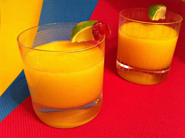 Two Glasses Filled With Juice And Garnish With Lime Wedges And Raspberries On A Red, Blue And Yellow Table Mats.