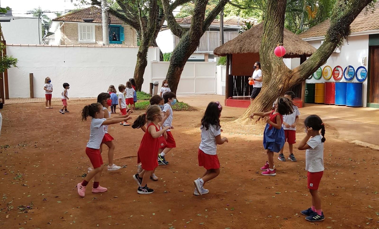 A imagem mostra um grupo de crianças jogando bola em um quintal de terra com árvores.