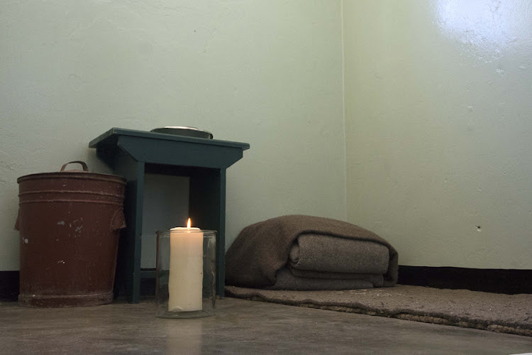 A candle burns on Sunday in Nelson Mandela's cell on Robben Island, three days after he died in Johannesburg at the age of 95. Picture: TREVOR SAMSON