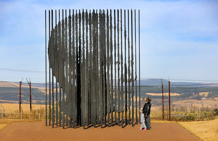 Anti -apartheid activist Monty Naicker's nephew Thumbi Naicker takes his grand daughter Amber Naicker to the Mandela Monument in Howick at the place where Mandela was captured on his way to Johannesburg.
