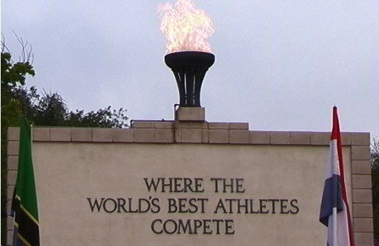 The stone plaque with Olympic flame and international flags gracing the first turn at Mt. SAC.  Photo by John Dye.