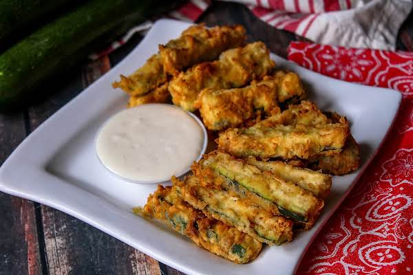 A Plate Of Fried Zucchini With Dipping Sauce.