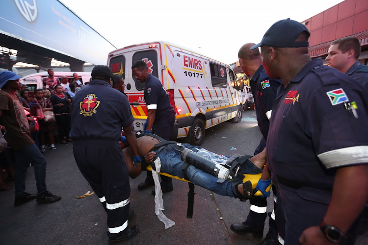 Paramedics carry the badly injured man to an ambulance at the Pinetown Taxi Rank.
