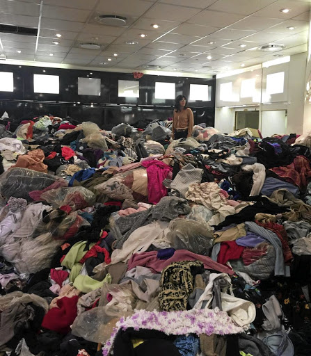 A volunteer stands thigh-deep in donations meant for those who lost their homes and belongings in the fire.