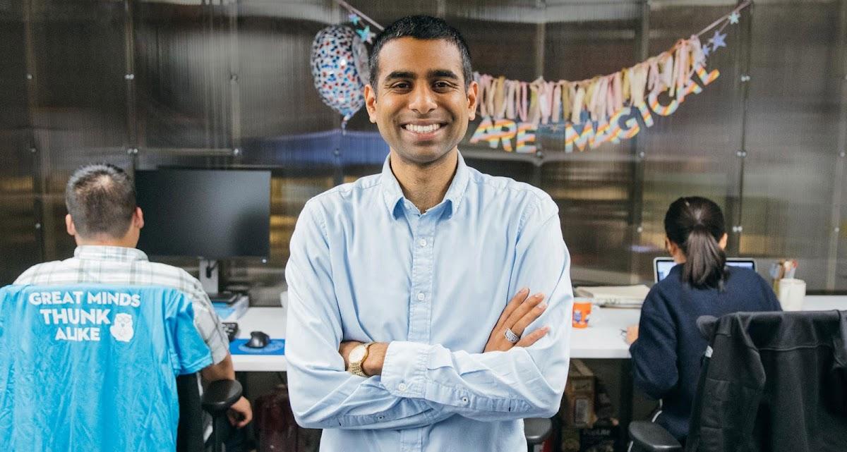 Arun Saigal, fundador de Thunkable, aparece de pie con los brazos cruzados mientras, detrás de él, dos compañeros de trabajo están sentados a sus mesas.