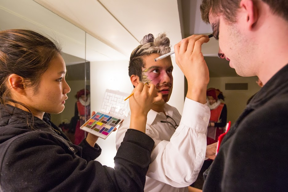 Students apply each other's stage makeup for a theatrical production