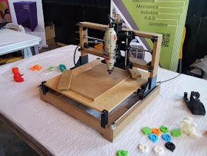 Photo: Impresora modificada, con una fresadora acoplada marcando letras sobre madera.