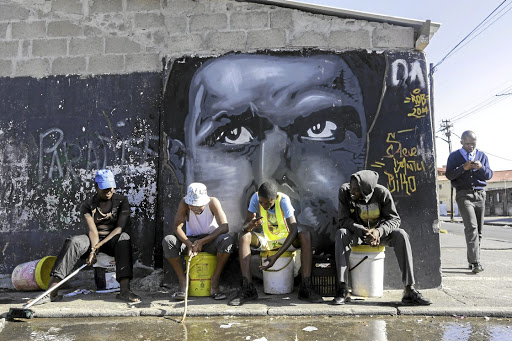 Class system: A group of youngsters in Langa, Cape Town, relax against a wall bearing a painting of Steve Biko.  Picture: DAILY DISPATCH