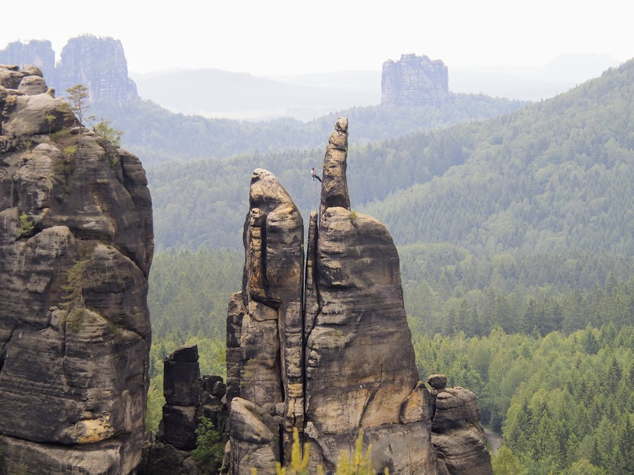 A climber rappelling down after a climb in Saxony-Switzerland