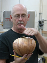 Photo: John talks about how he designs his carving to fit the flow of the wood grain.