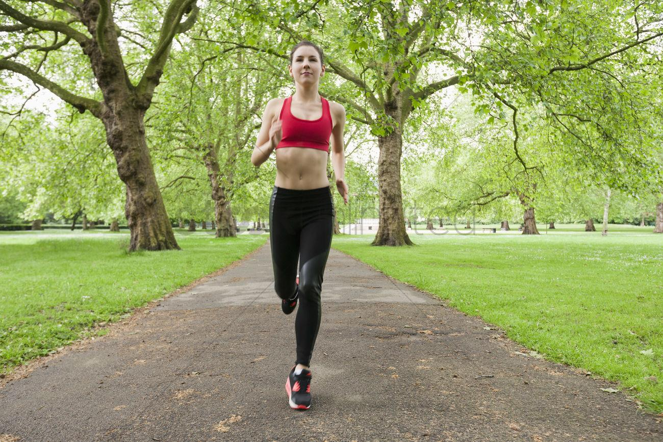 Full length of fit young woman jogging in park Stock Photo ...