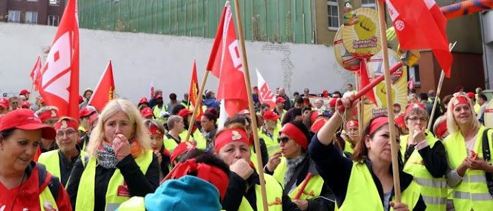 Demonstrantinnen mit IG-Bau-Fahnen, Trillerpfeifen und Symbolschildern.