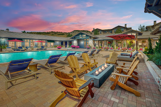 Montrachet Denver West community pool at dusk with seating around a fireplace