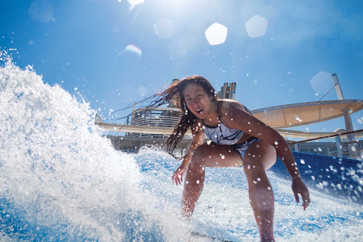 A girl tries out some moves on the FlowRider surfing simulator on Harmony of the Seas.