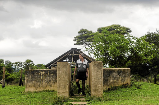 LANDLESS The former president of Zimbabwe's Commercial Farmers' Union, Deon Theron, inspects a disused cattle dip on his farm where he ran a successful dairy before being forced off the property Picture: Jekesai Njikizana/AFP