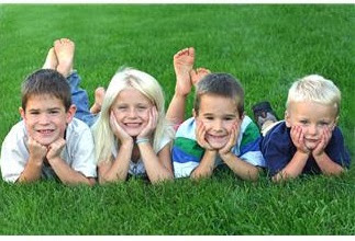 Kids lying on grass with heads in hands