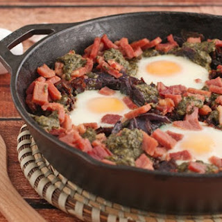 Skillet Baked Eggs with Potatoes, Pesto & Sun Dried Tomatoes