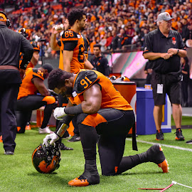Taking A Knee by Garry Dosa - Sports & Fitness American and Canadian football ( orange, sports, teams, players, indoors, black, cfl, stadium, football, people, kneeling )