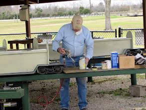 Photo: Bob Barnett working on his spray gun that is plugging up.    2014-0104 RPW