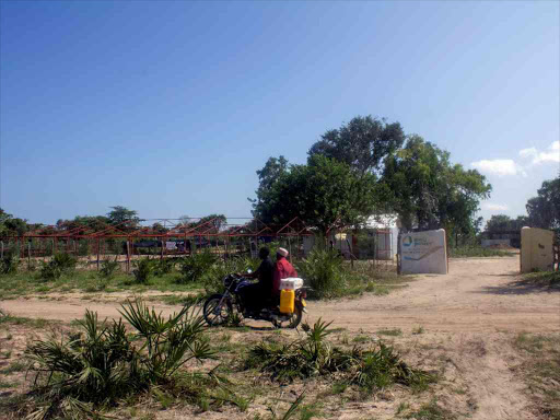 Residents ride a motorbike past the proposed site of the coal plant in Kwasasi village, near Lamu.