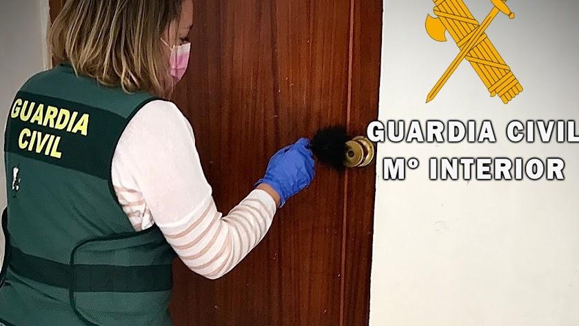 La Guardia Civil inspecciona la puerta forzada.
