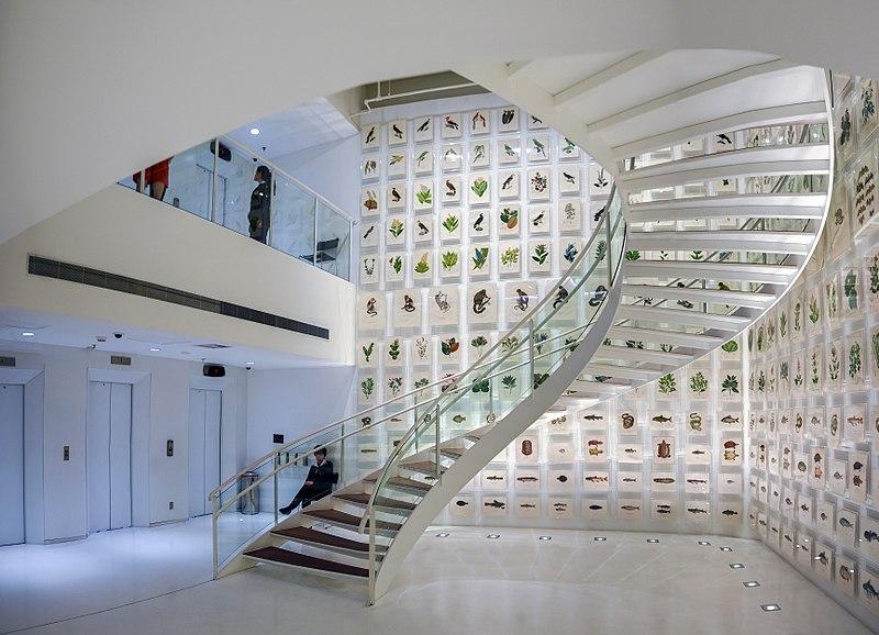 Vista interna do Itaú Cultural, enfeitado com pequenos quadros com animais e escadaria espiral para o segundo andar.