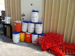 Photo: Water coolers 5 gallon; orange safety fencing