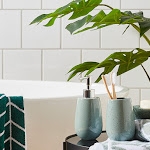 Bathroom side table with a blue dispenser and tumbler, green printed towels and an artificial plant in the background