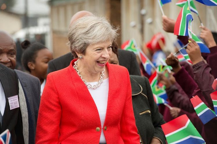 Britain's Prime Minister Theresa May is greeted by schoolchildren waving British and South African flags, during a visit to the ID Mkhize Secondary School in Gugulethu township, Cape Town, on August 28 2018, as part of a three-nation visit to Africa.