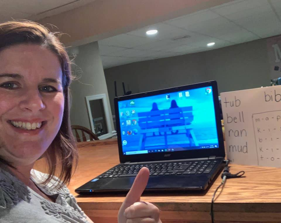 Holy Cross teacher gives thumbs-up sign while teaching remotely.