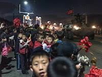 kinderen met rode bloemen op straat bij avond kijkend naar langsrijdende militaire voertuigen