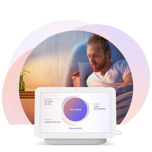 [Image] A man is sitting upright in bed turning toward his Nest Hub display at his bedside. It shows personalised insights about his sleep.
