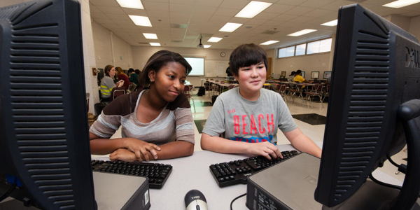 Two students working on desktop computers