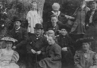 Photo: Centrale figuur hier is de oudere heer met hoed, Willem Frederik Hesselink (1846-1927). Helemaal rechtsboven zijn schoondochter Berta Güettler (1882-1946), naast haar zijn dochter Seraphina Hesselink (1872-1954), gehuwd met de blonde man met baard Hendrik Frits Julius (1871-1945). De drie kinderen behoren bij dit echtpaar. Helemaal rechtsonder dochter Egberdina Anna Hesselink (1882-1975). De oudere dame in het zwart is Egberta Engberts (schoonzuster van Willem Frederik), de man links met hoed is haar zoon Engbertus Hesselink (1879-1930), met aan zijn voeten zijn vrouw Hendrika Elisabeth Catharina van de Kamer (1874-1967). Tenslotte midden onder Egberdina Anna Hesselink (1884-1976), de zuster van Engbertus. De foto is van ca. 1907.
