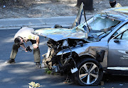 Los Angeles County Sheriff's Deputies inspect the vehicle of golfer Tiger Woods, who was rushed to hospital after suffering multiple injuries, after it was involved in a single-vehicle accident in Los Angeles, California on February 23, 2021.
