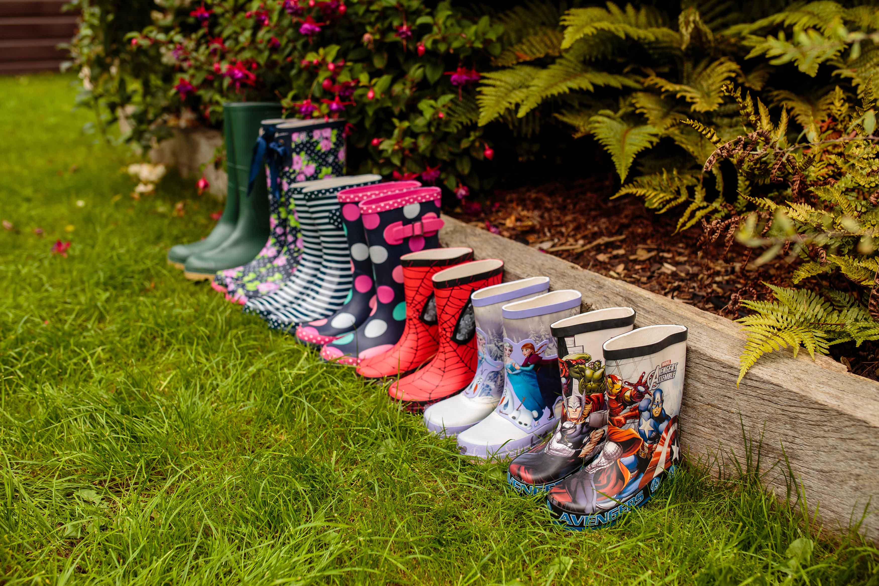 Row of colourful wellies on grass