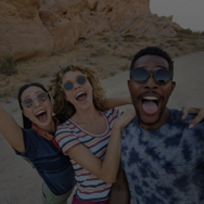 Three friends posing for a group selfie outside