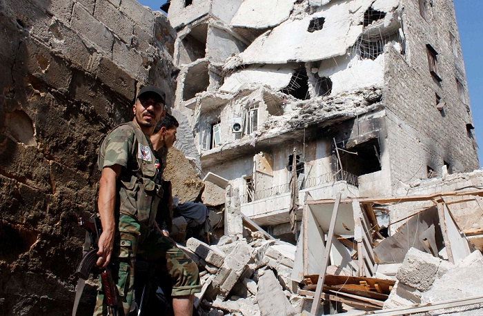 HARD HIT: Free Syrian Army fighters stand in front of buildings damaged during shelling by forces loyal to Syria's President Bashar al-Assad in Aleppo in this file image. Picture: REUTERS