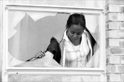 SHATTERED: Resident Maite Matima looks through the broken window suspected to have been used by illegal Zimbabweans to get into her house in Serala View, Polokwane. Pic: ELIJAR MUSHIANA. 19/11/2009. © Sowetan.