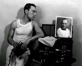 Photo: Even Buster Keaton could be roped into being presented half-dressed.  Here Keaton regards a publicity photo of Lon Chaney Sr., a great horror star who was the antithesis of glamour: Chaney transformed himself ruthlessly into various monstrous characters.  This is a kind of meta-portrait, in which one not-very-glamorous star regards another even-less-glamorous star, wearing similar attire.  But Keaton's body is presented to us for delectation in a way that Chaney's never was.  It's hard to imagine a woman being photographed in a similar way in this period.