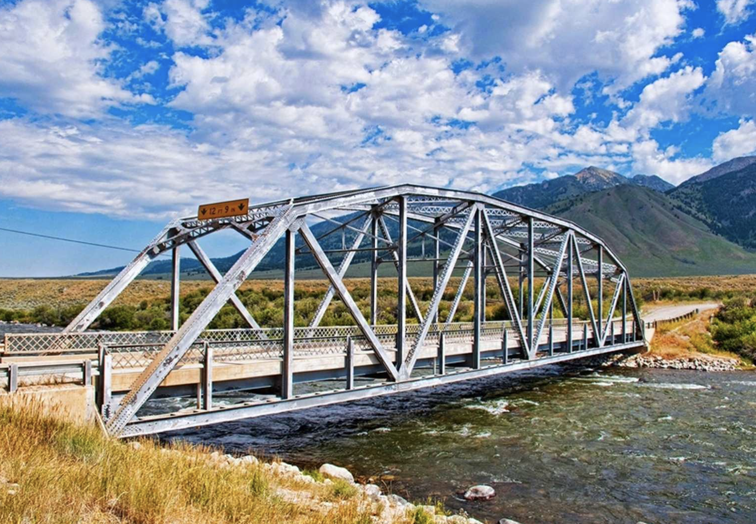 Bridge over river at campground in Montana with mountains in background