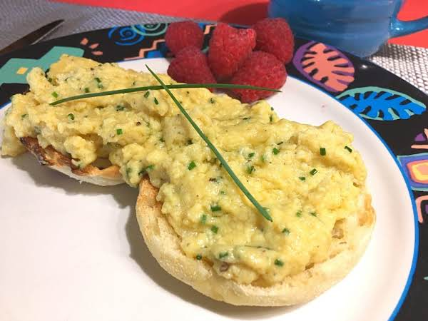 Scrambled Eggs On English Muffins Garnished With Chives And Raspberries.