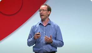 Man in blue shirt presenting on stage