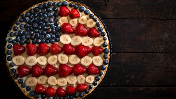 an all-American pie decorated like a flag with fruit toppings.