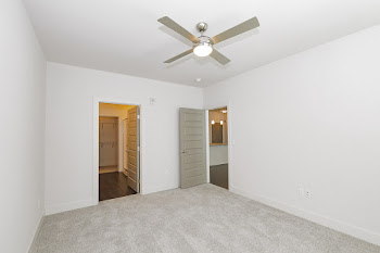 Bedroom with carpet and ceiling fan and attached bathroom