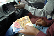 The writer says when travelling by minibus, she avoids sitting by the taxi driver because the 'honour' of counting change falls on whoever sits there.