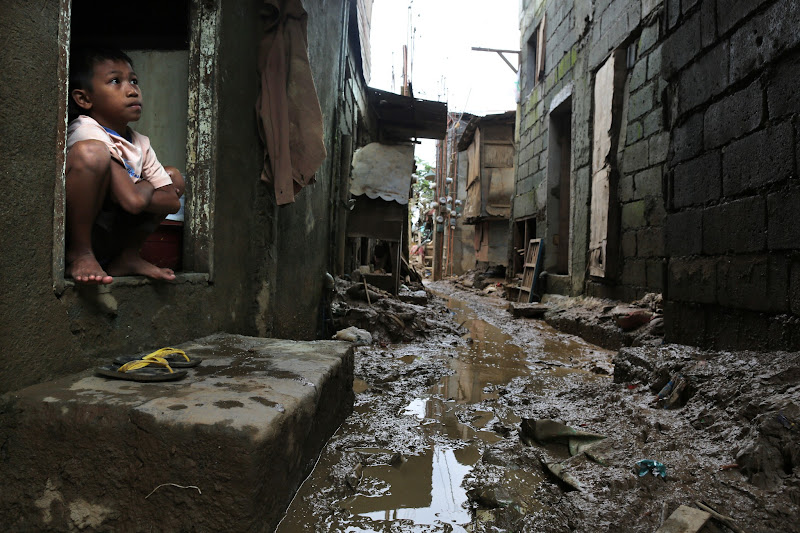 Photo: MANILA, PHILIPPINES - AUGUST 12: A boy looks out of his home in a low lying community covered in mud August 12, 2012  in Manila, Philippines. The weather is slated to deteriorate as another low pressure system is expected to hit the region in the next 24 to 48 hours causing the waters to rise again. According to the Office of Civil Defense the floods left at least 66 people dead and affected up to 2.68 million people in Manila and surrounding provinces, with more than 440,000 fleeing to evacuation centers. (Photo by Paula Bronstein/Getty Images)